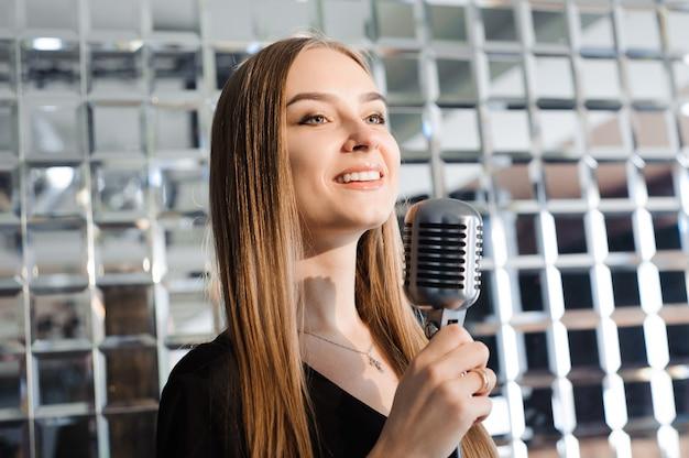 Fiesta de karaoke. chica de belleza con un micrófono cantando.