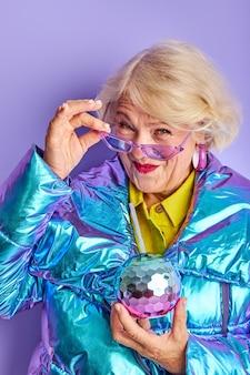 Fiesta mujer de 60 años aislada en estudio en espacio púrpura, dama senior en anteojos y abrigo colorido preparándose para la fiesta, diviértase