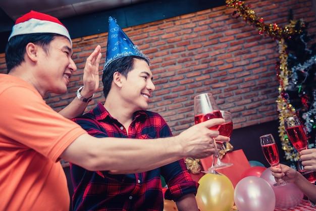 Fiesta de navidad y año nuevo con amigos. pareja gay bebiendo vino tinto en la noche de vacaciones.