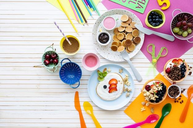 Fiesta de panqueques, comida para niños con bayas frescas y yogur