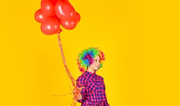 Fiesta de san valentín. niño use peluca arcoiris pelo fondo amarillo. niño feliz mantenga globos de fiesta. globos de corazón para el día del amor. sorpresa para san valentin. colorido y brillante. niña pequeña con peluca.