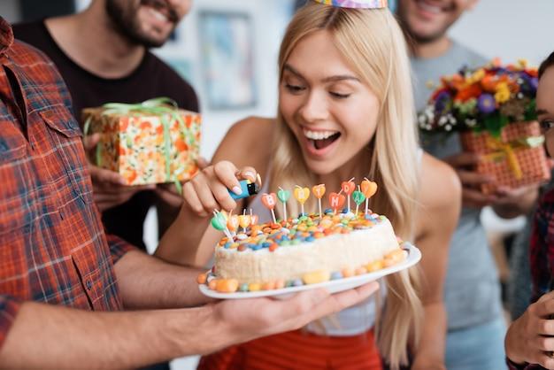 Fiesta sorpresa de cumpleaños. niña enciende velas.