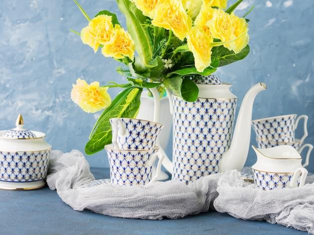 Fiesta de té de pascua conjunto festivo y flores amarillas.