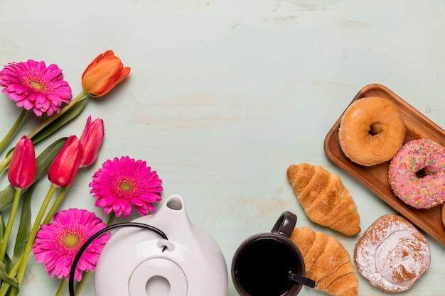 Fiesta de té con pastelería y flores.