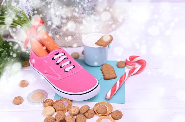 Fiesta tradicional holandesa para niños sinterklaas. pepernoten y dulces tradicionales estroboscópicos, zanahoria en una bota y leche con galletas.