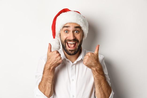 Fiesta, vacaciones de invierno y concepto de celebración. hombre disfrutando de la navidad, vistiendo gorro de papá noel y mostrando el pulgar hacia arriba con cara emocionada