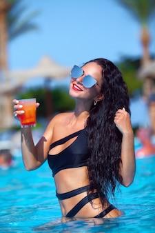 Fiesta de verano, sexy mujer joven con cabello largo bebiendo cócteles