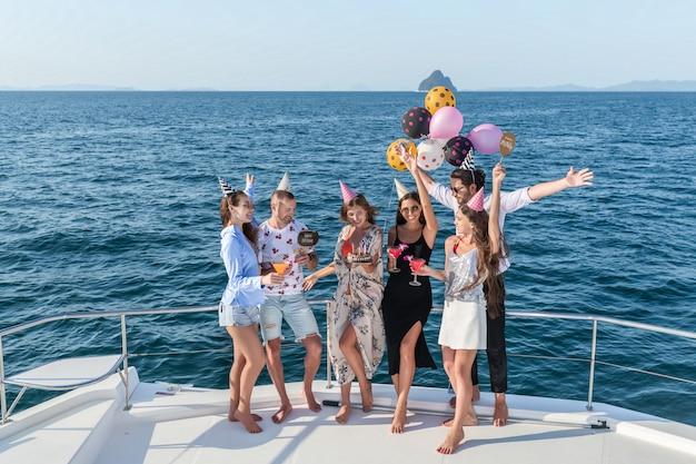 Fiesta en un yate. una compañía de jóvenes celebra su cumpleaños durante un crucero marítimo.