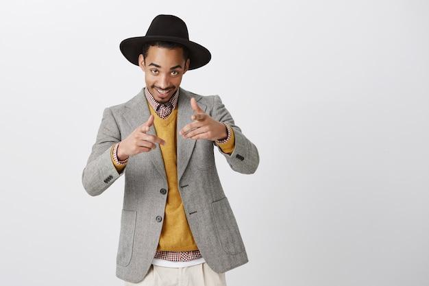 Un fiestero emotivo que nos invita al club. retrato de hombre de negocios atractivo positivo con elegante sombrero y chaqueta, coqueteando o siendo macho, apuntando con gesto de pistola, de pie sobre una pared gris