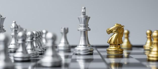 Figura de ajedrez de oro y plata en tablero de ajedrez contra oponente o enemigo.