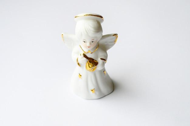 Figura de ángel de cerámica sobre un fondo blanco.