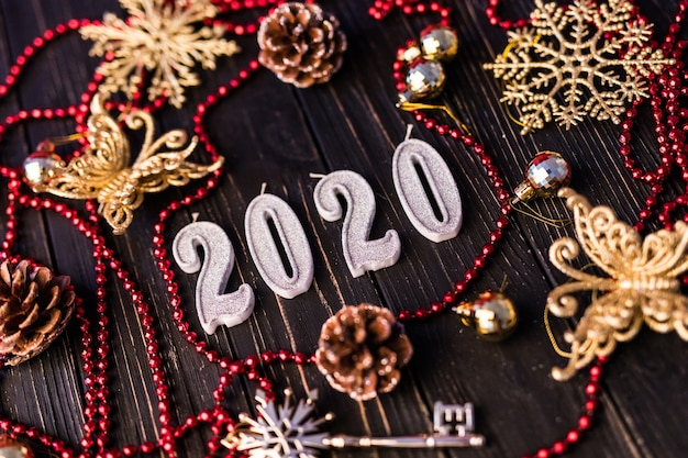Figura de año nuevo de collar rojo. ramas de abeto sobre tablas de madera, vista superior. adornos navideños sobre fondo de madera. copia espacio
