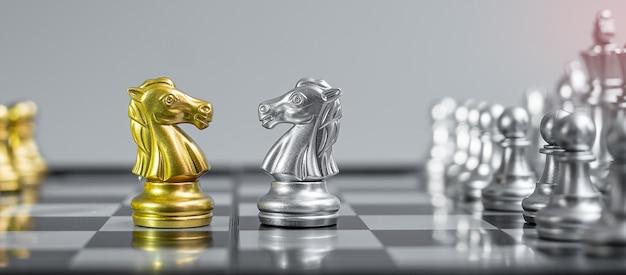 Figura de caballero de ajedrez de oro y plata en tablero de ajedrez contra oponente o enemigo.