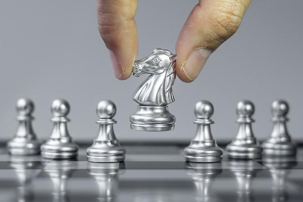 Figura de caballero de ajedrez plateado destaca entre la multitud en el fondo del tablero de ajedrez.