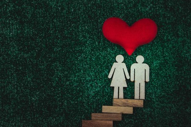 Figura de madera hombre y mujer con un corazón en concepto de amor y salud.