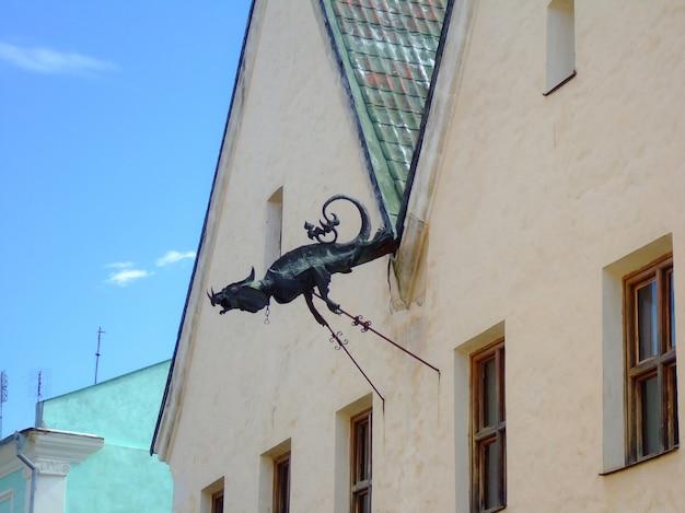 Una figura decorativa de hierro de una quimera mítica está instalada en la fachada de una casa antigua
