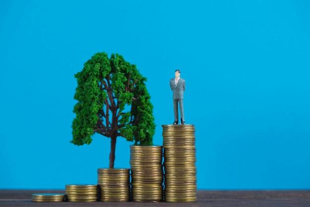 Figura empresario en miniatura en pila de monedas con arbolito