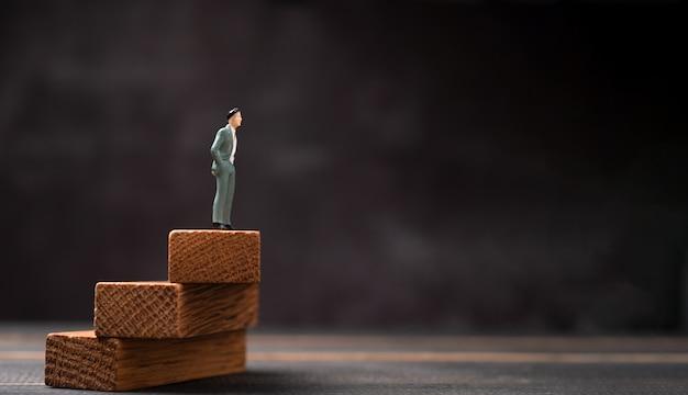 Figura empresario de pie sobre un soporte de madera y mirando hacia el futuro.