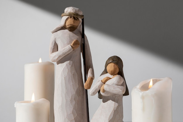 Figura femenina y masculina del día de la epifanía con velas y recién nacido