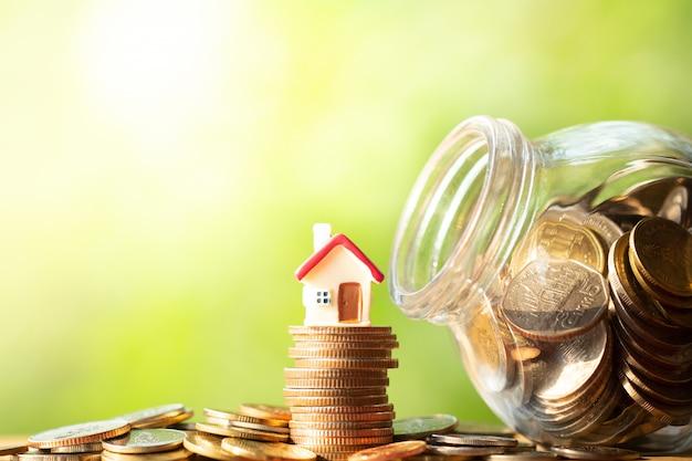 Figura de forma de casa roja en pila y pila de monedas
