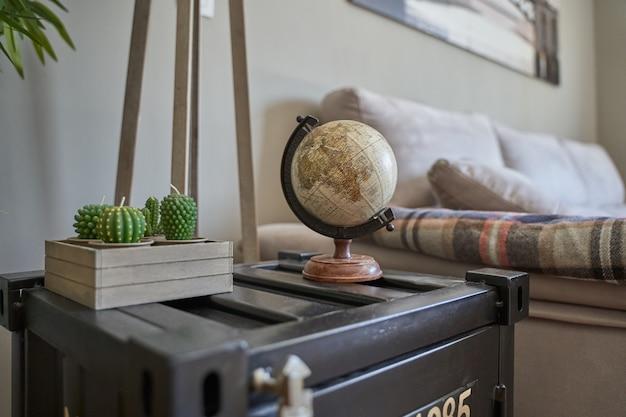 Figura de globo terráqueo en el estante junto a una planta junto a la cama