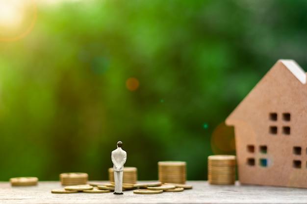 Figura de hombre de negocios en miniatura de pie para ver el futuro frente a monedas de oro.