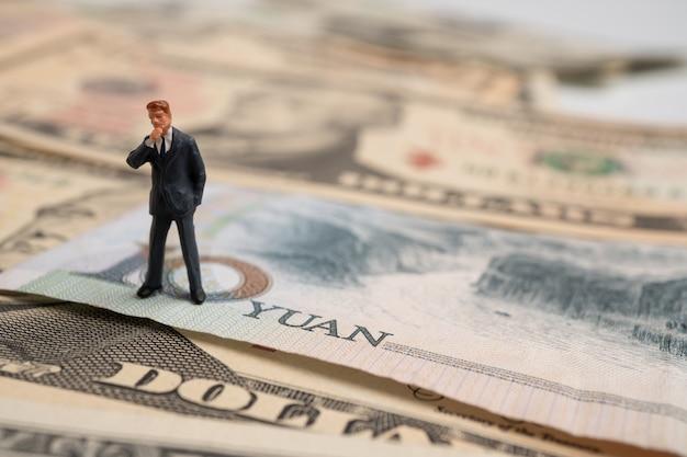 Figura hombre de negocios de pie en el billete de yuan en dólares estadounidenses y pensando.