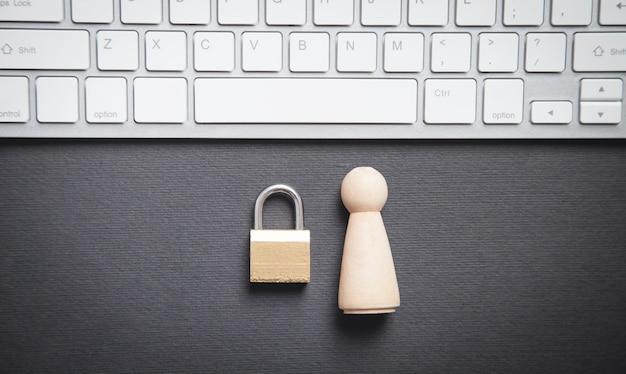Figura humana de madera con un candado y un teclado de computadora.