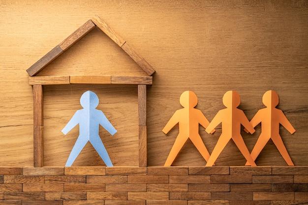 Figura humana de recorte de papel azul dentro de un bloque de madera hecho a casa y otras tres figuras de recorte de papel naranja fuera de la casa de madera en la pared de madera