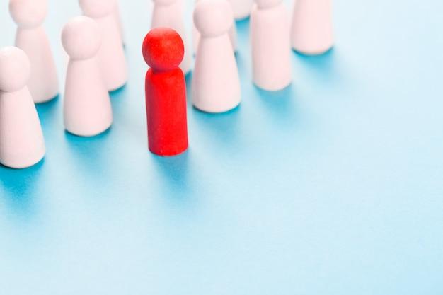 Figura humana roja cerca de figuras humanas blancas.