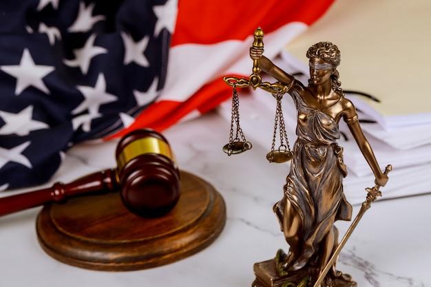 Figura de justicia sosteniendo la balanza de la justicia con martillo en una ley documentos en papel bandera de los estados unidos