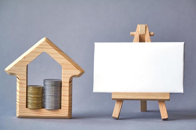Figura de madera de la casa con dos columnas de monedas en el interior y pizarra