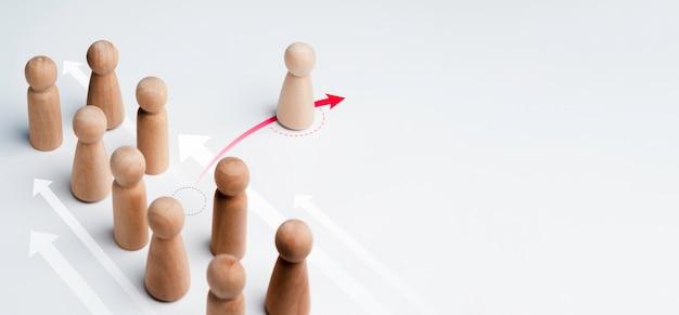 La figura de madera de pie sobre la flecha roja, cambia de dirección y apunta de manera diferente al grupo sobre fondo blanco con espacio de copia. liderazgo, negocio único, concepto de solución innovadora.
