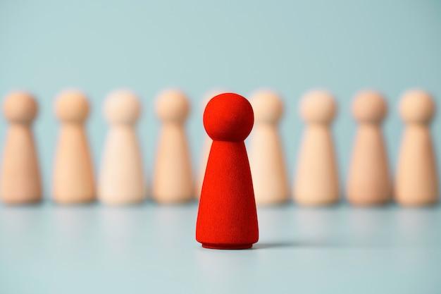 Figura de madera roja de pie delante de otras figuras sobre fondo azul, concepto de liderazgo y gestión.