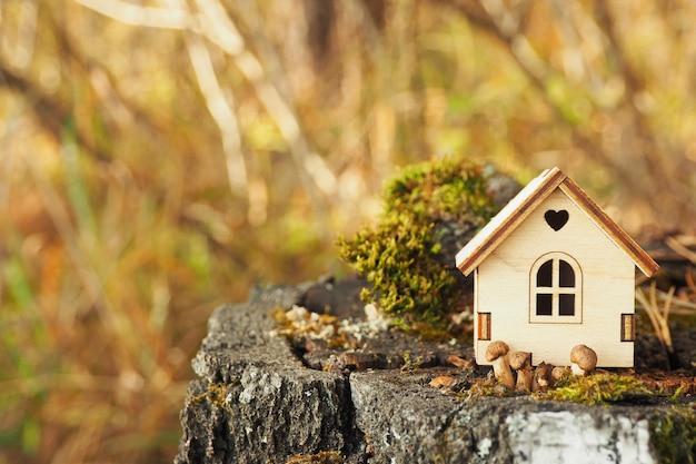 Una figura en miniatura de una casa de madera sobre un tocón de abedul con musgo y pequeños hongos.