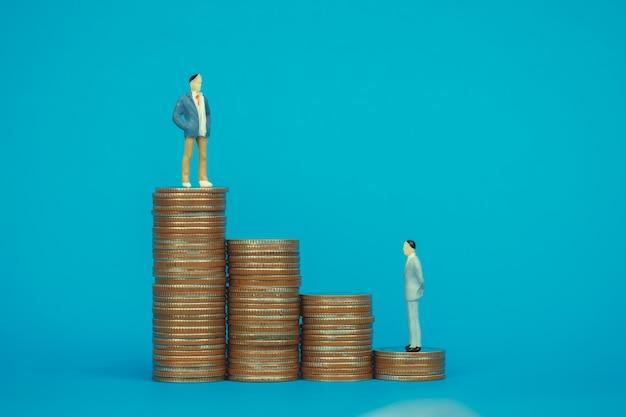 Figura miniatura empresario de pie en la pila de monedas