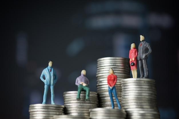 Figura miniatura empresario de pie sobre la pila de monedas