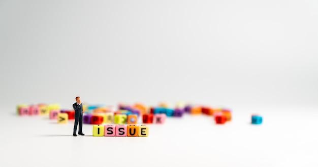 Figura miniatura de hombre de negocios de pie al lado de issue alfabeto y pensamiento