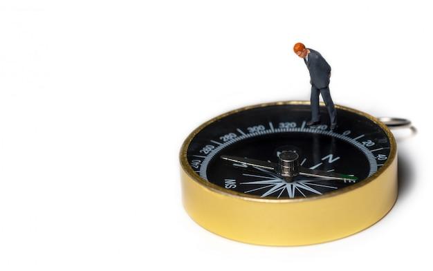 Figura miniatura de hombre de negocios de pie en el compás de oro para encontrar el camino