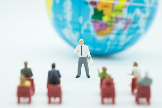Figura miniatura de hombre de negocios presente en frente de la habitación con una mini bola mundial.