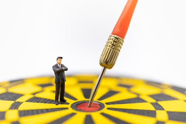 Figura miniatura del hombre de negocios que se coloca y que mira para lanzar la puñalada en el centro del tablero de dardo negro y amarillo.