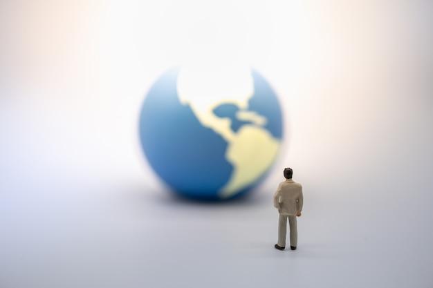 Figura miniatura del hombre de negocios que se coloca y que mira a la mini bola del mundo.