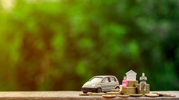 La figura miniatura del hombre de negocios se sienta en monedas de oro y un modelo del coche.