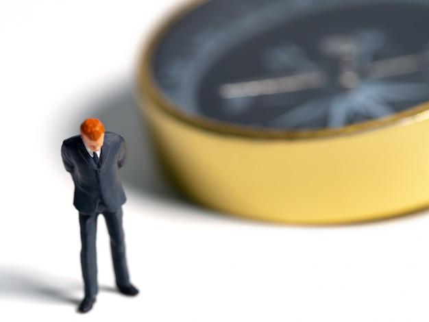Figura miniatura de hombre de negocios en traje azul oscuro de pie en el lado de la brújula dorada