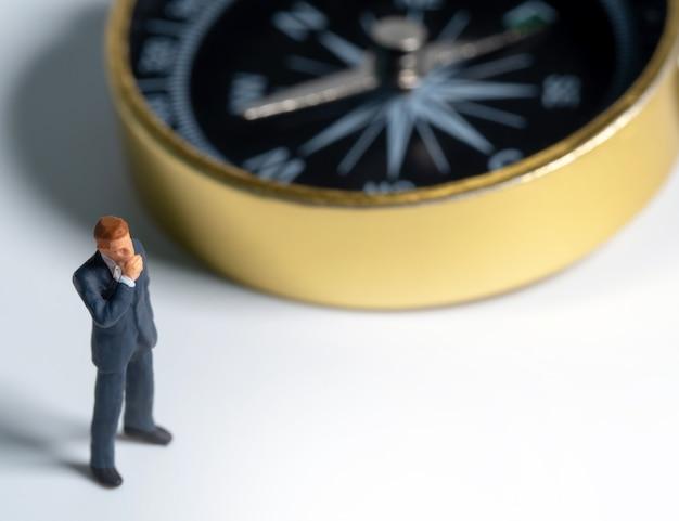 Figura miniatura de hombre de negocios en traje azul oscuro de pie en el lado de la brújula dorada.