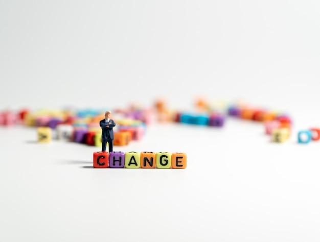 Figura miniatura de hombre de negocios en un traje azul oscuro que se encuentra en la parte trasera del colorido del cambio