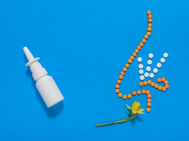 La figura de una nariz de tabletas inhala el aroma de una flor amarilla.