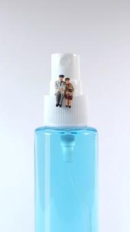 Figura de pareja de ancianos sentada en una botella de spray de alcohol. concepto covid-19.