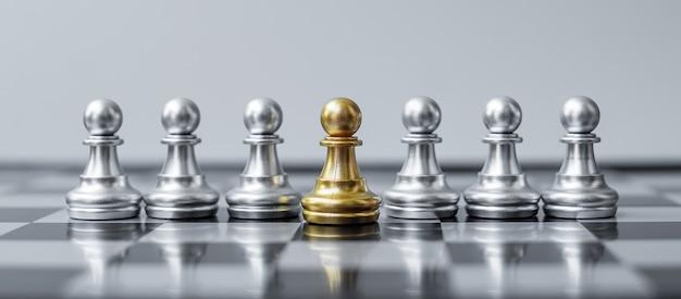 Figura de peón de ajedrez de oro destaque entre la multitud en el fondo del tablero de ajedrez.