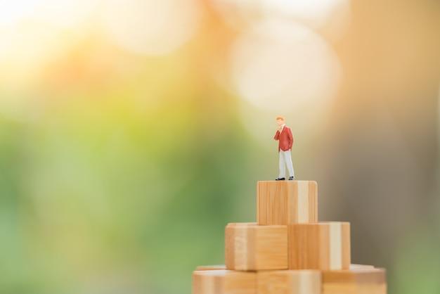 Figura de pequeño empresario de pie en el bloque de madera superior.